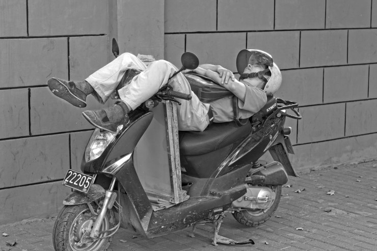 A man sleeping on a motorbike in China