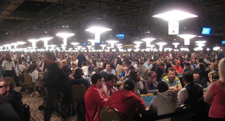 wsop event - poker room with many tables filled with players